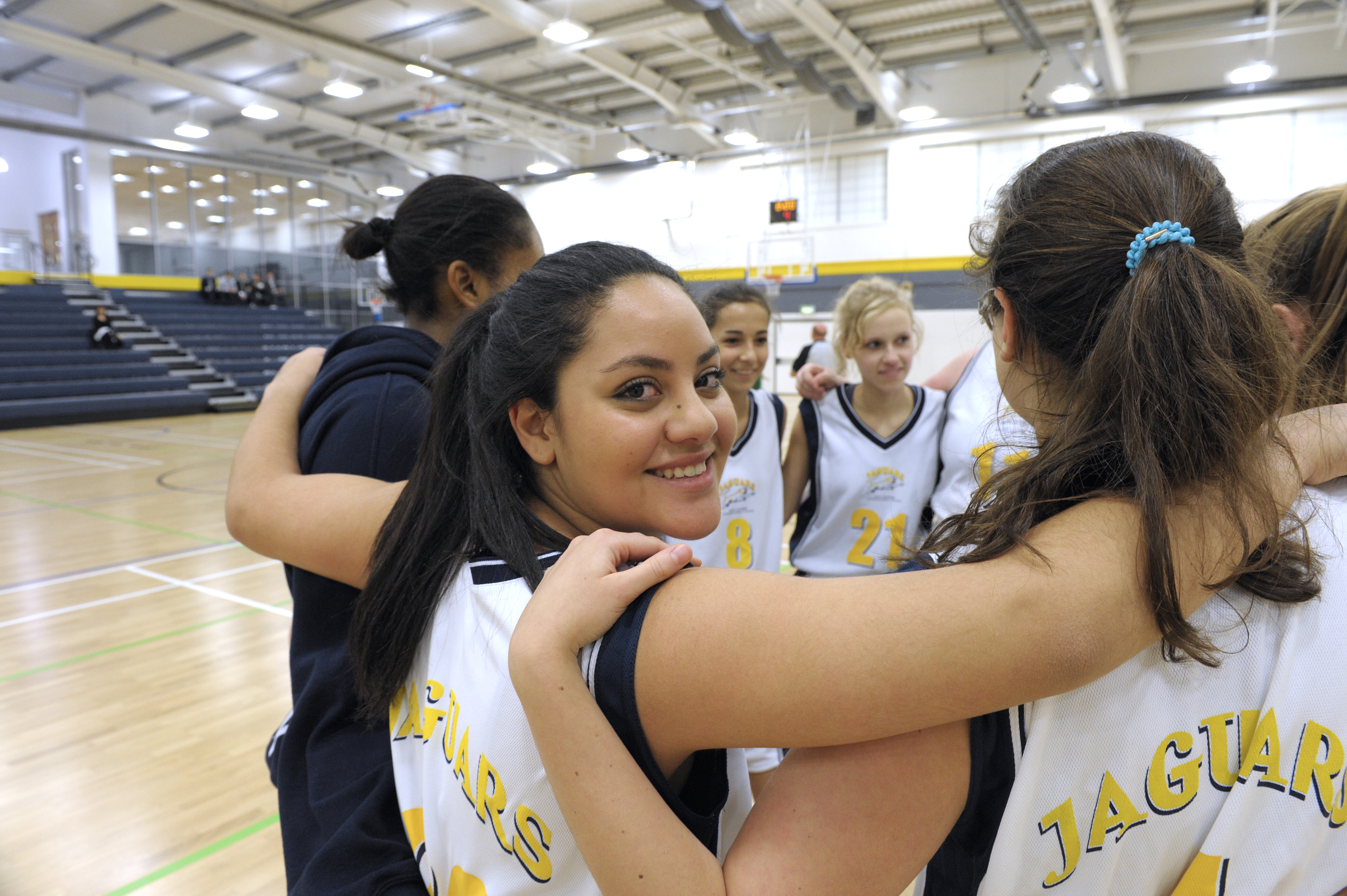ACS Egham Girls Basketball team in group huddle
