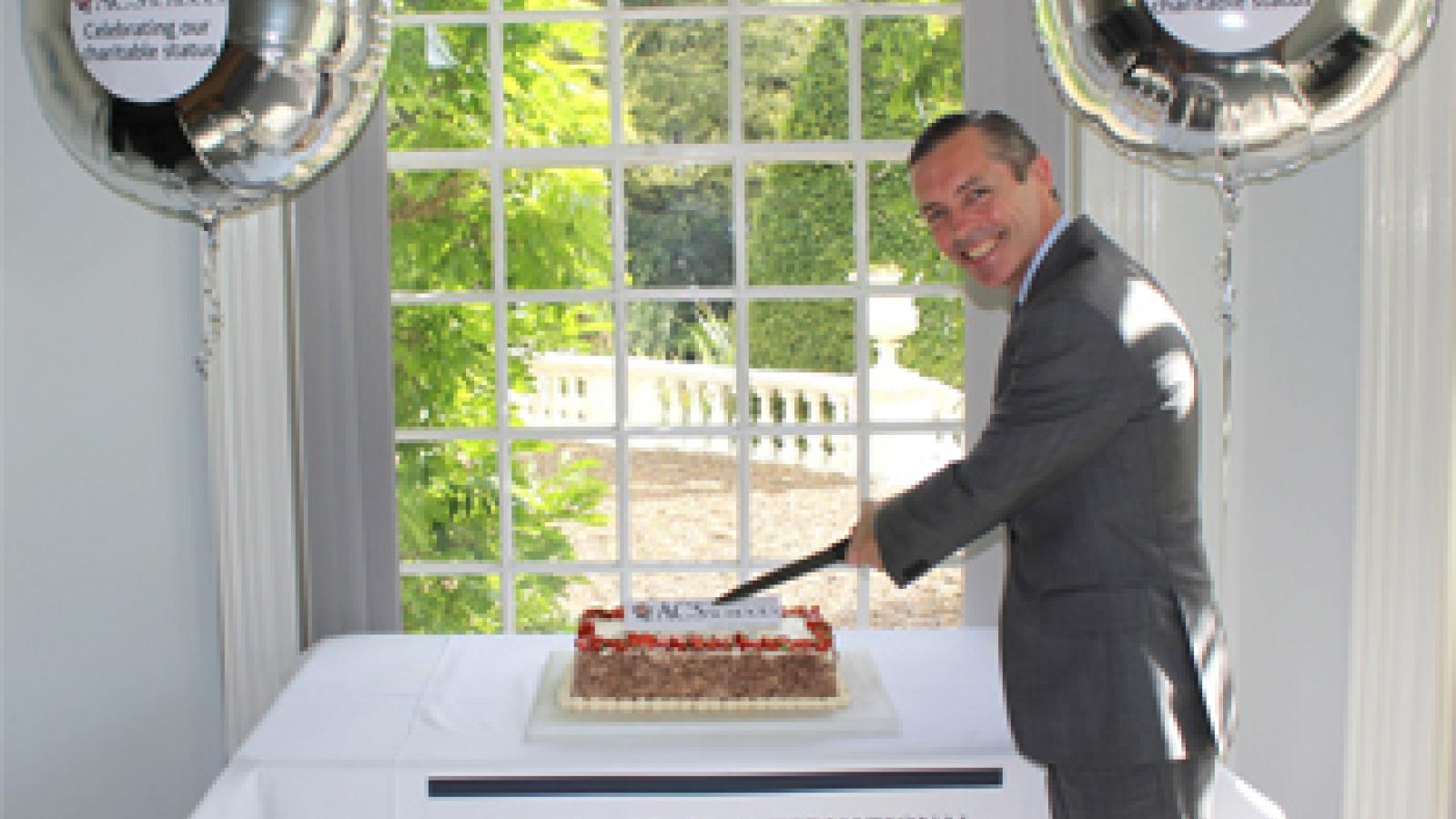 ACS International Schools CEO, Tim Cagney, cutting the cake during celebrations