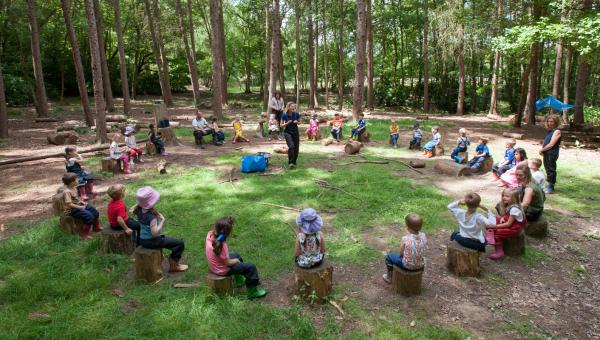 Early Childhood students sat in a circle in a forest