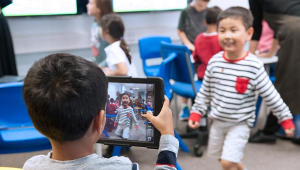 Lower School student using iPad to take photo of another student
