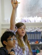 Student raising their hand in classroom