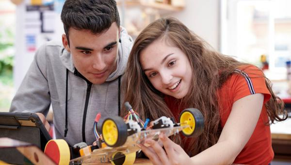 Two students building a remote controlled car