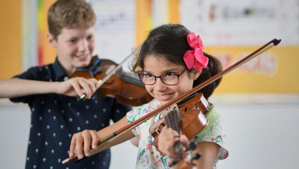 Two music students playing the violin