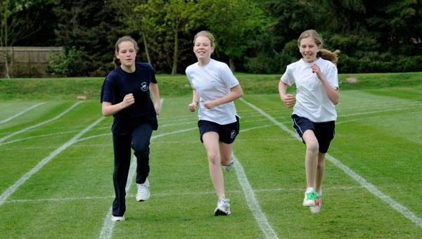 Three Egham student running on a running track