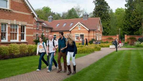 Students walking through the ACS Egham campus grounds