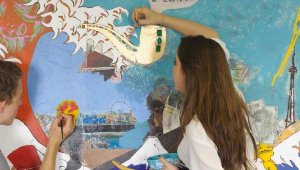 Two students paint a mural in art class