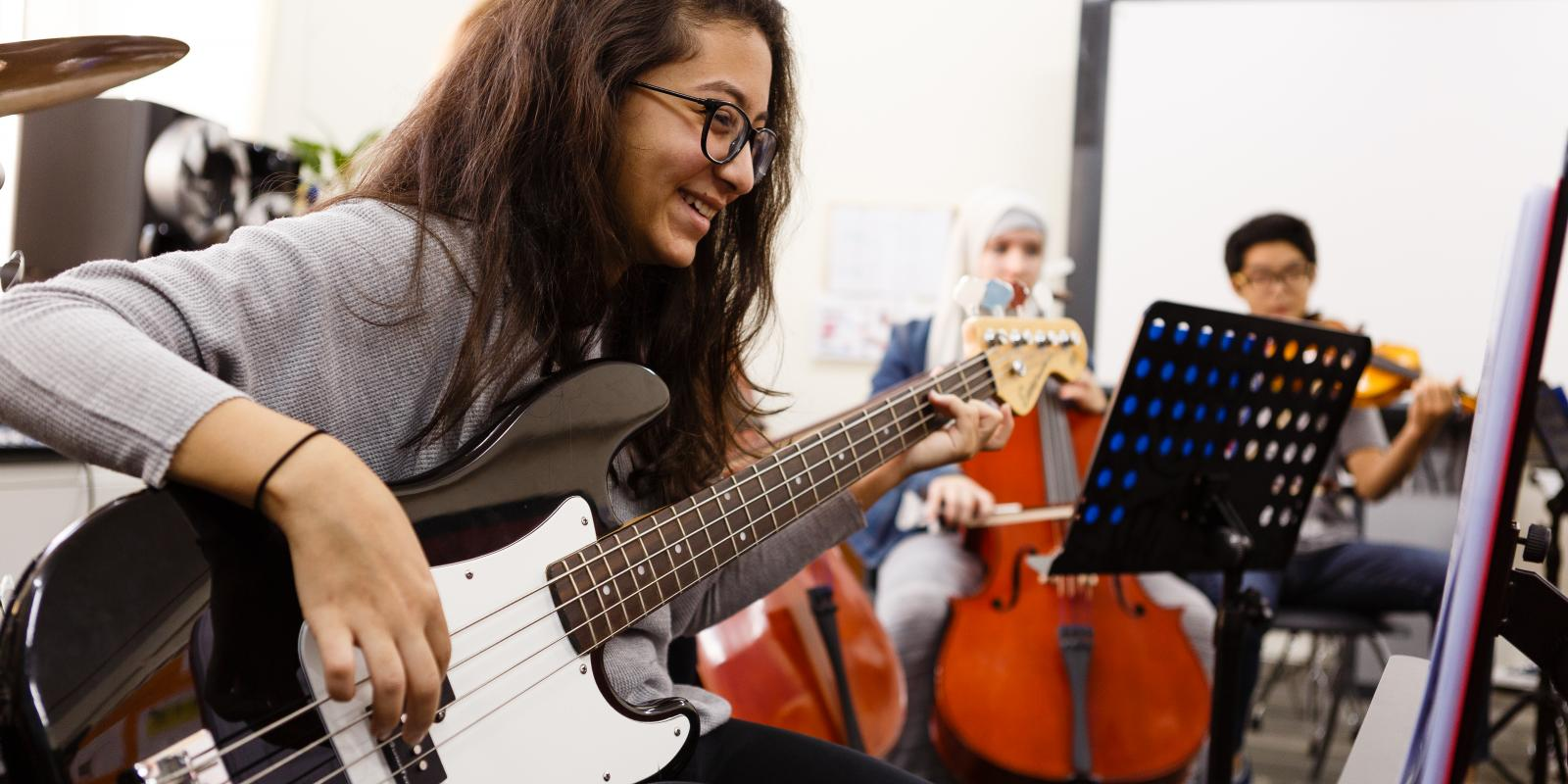Music facilities ACS Doha student with guitar