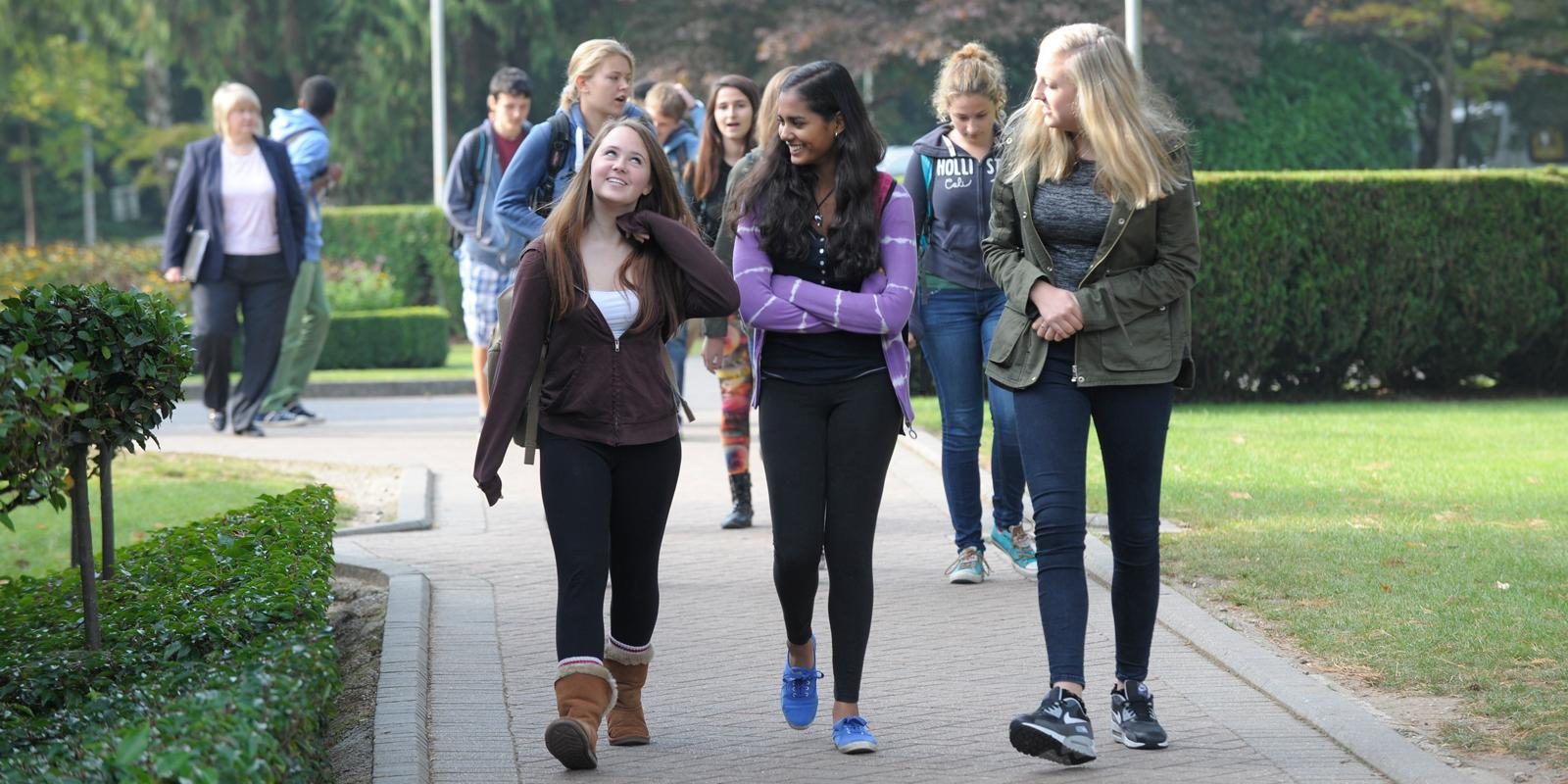 Three Egham students walking through the campus, smiling.