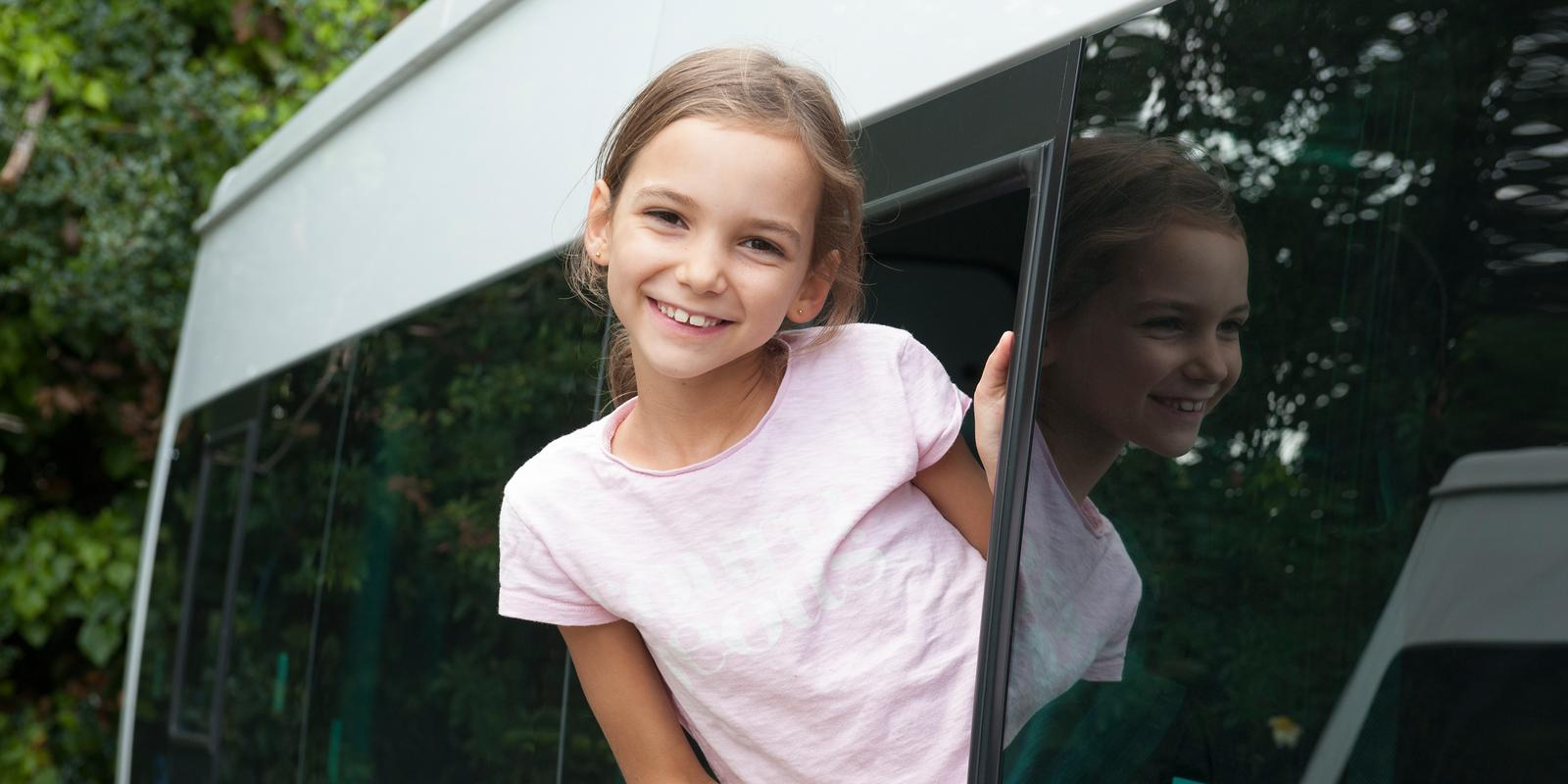 Student smiling whilst getting on a school bus