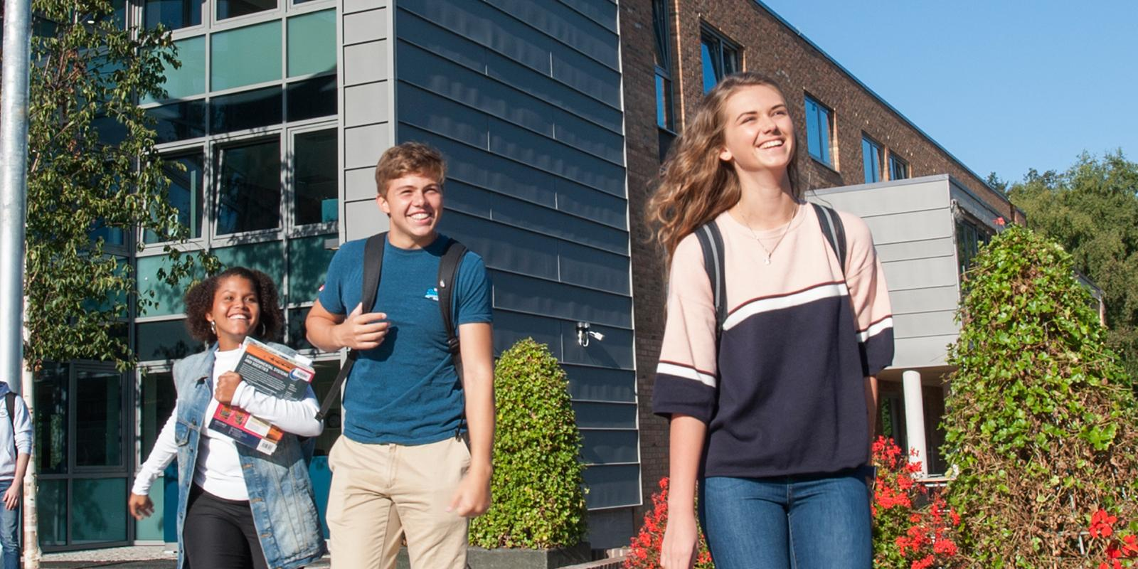 Smiling students walking together out of ACS Cobham campus building
