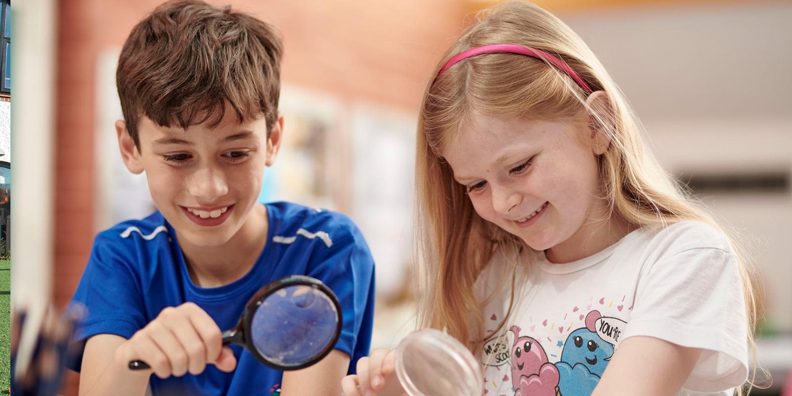 Two students play with magnifying glass