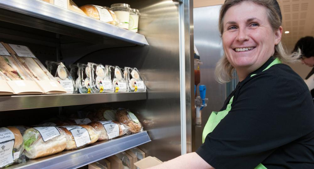 ACS Cobham catering assistant arranging the refrigerated food display