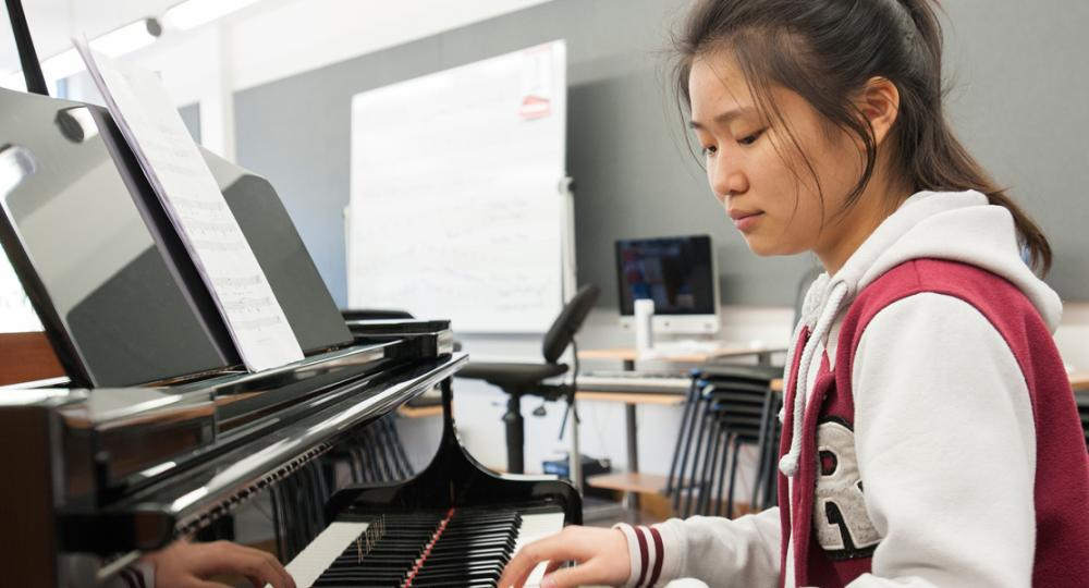ACS Cobham boarding student playing the piano
