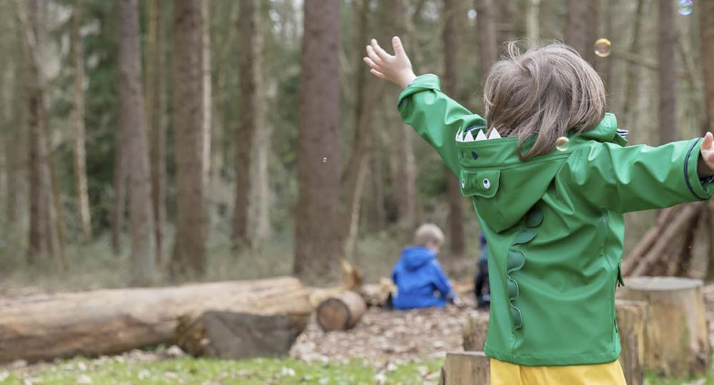 Child in waterproofs outside in Forest School