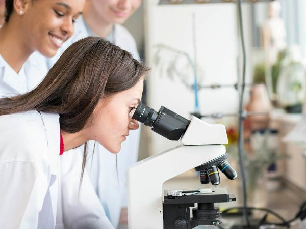 Students in a science lab with one looking into a microscope