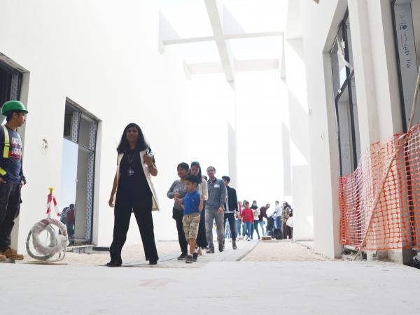 People walking along a corridor of the new ACS Doha site