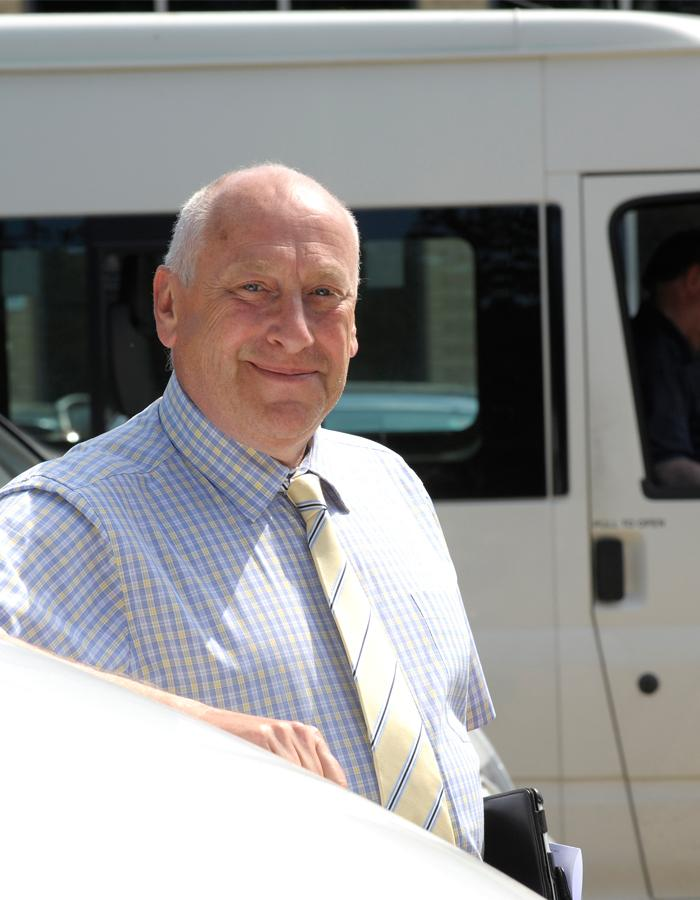 Hillingdon's Busing Officer stood beside a school bus