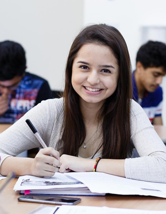 High school student sitting at desk smiling