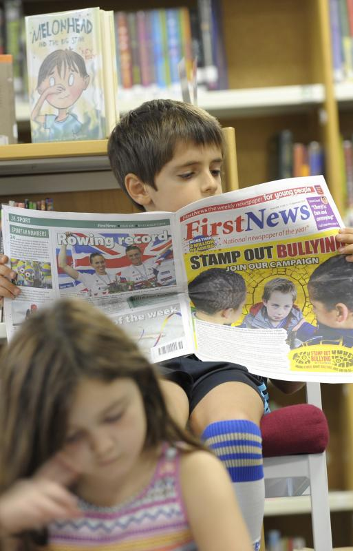 Lower School student reading the newspaper