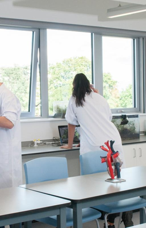 High School students work in white coats in the ACS Hillingdon science labs