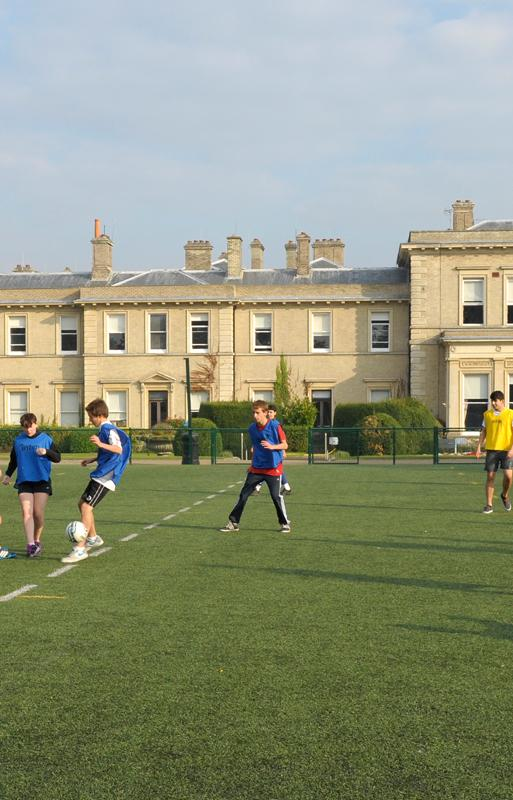 ACS Hillingdon students play football on grass pitch