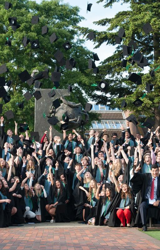 ACS Cobham Students throw mortarboards in the air at graduation