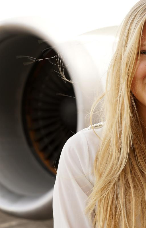 Girl smiles at the camera with an aeroplane engine in the background