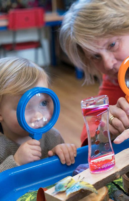 Child and woman both looking at something using magnifying glasses