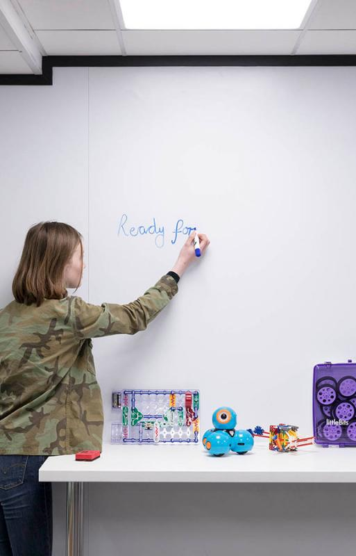 Girl writing the word ready on a whiteboard